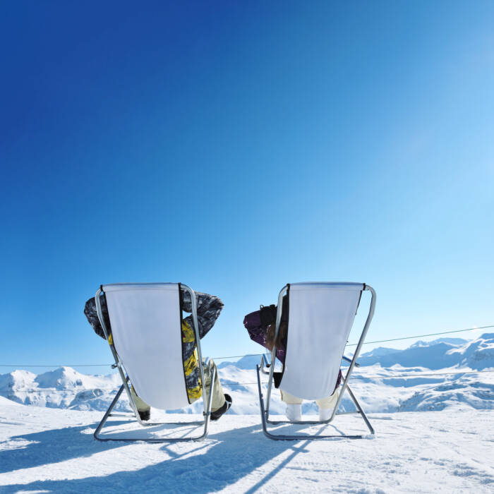 Two people on deck chairs on the mountain
